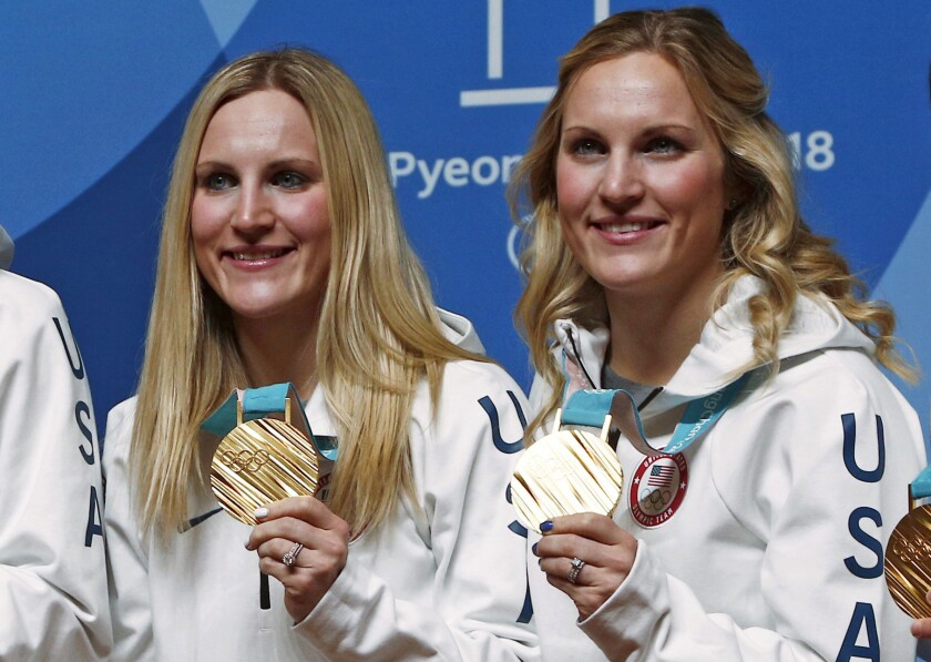 Team USA hockey players Monique Lamoureux-Morando and Jocelyne Lamoureux-Davidson celebrate after winning gold medals at the 2018 Winter Olympics.