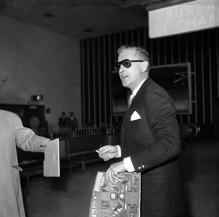 Stewart Granger smokes a cigarette at the airport in London in 1960