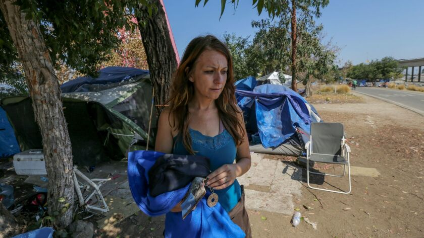 Jodi Samhat, 34, stands outside her tent at a homeless encampment along the Santa Ana River bed in A
