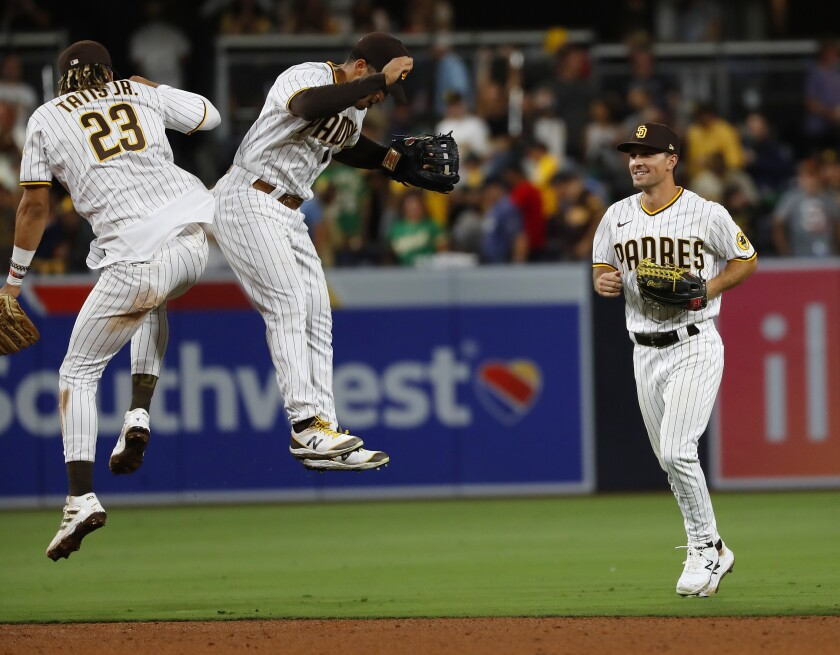 Padres' Fernando Tatis Jr., Trent Grisham, and Adam Frazier celebrate a win against the Oakland Athletics in July.