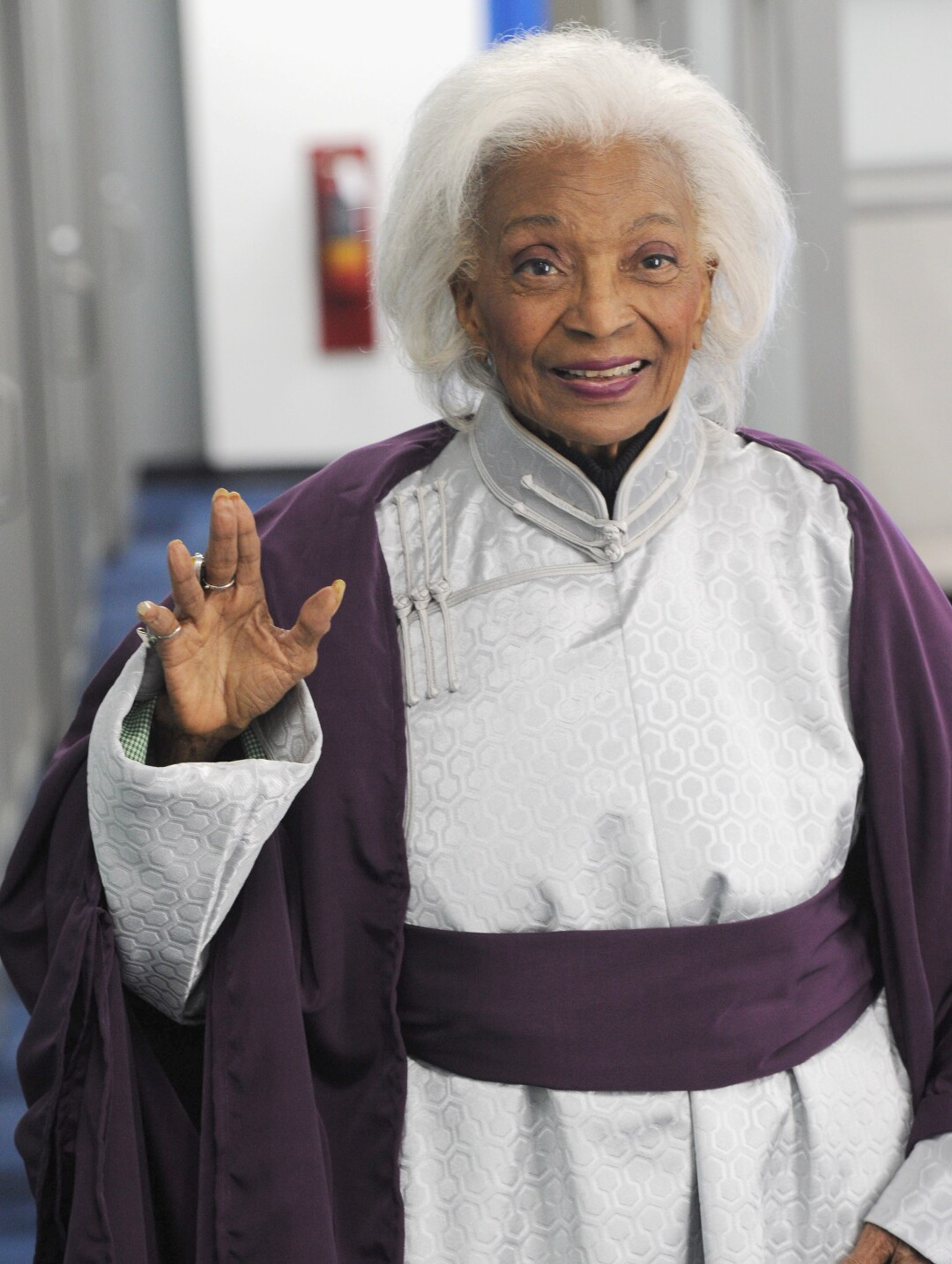 """A woman with white hair smiles and spreads her fingers in a """"Star Trek"""" symbol"""