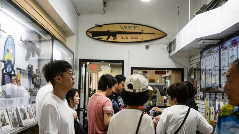 HONOLULU, HI - AUGUST 26: A Chinese tour group waits to fill out paperwork before entering the range