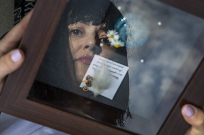A woman is reflected in a shadow box.
