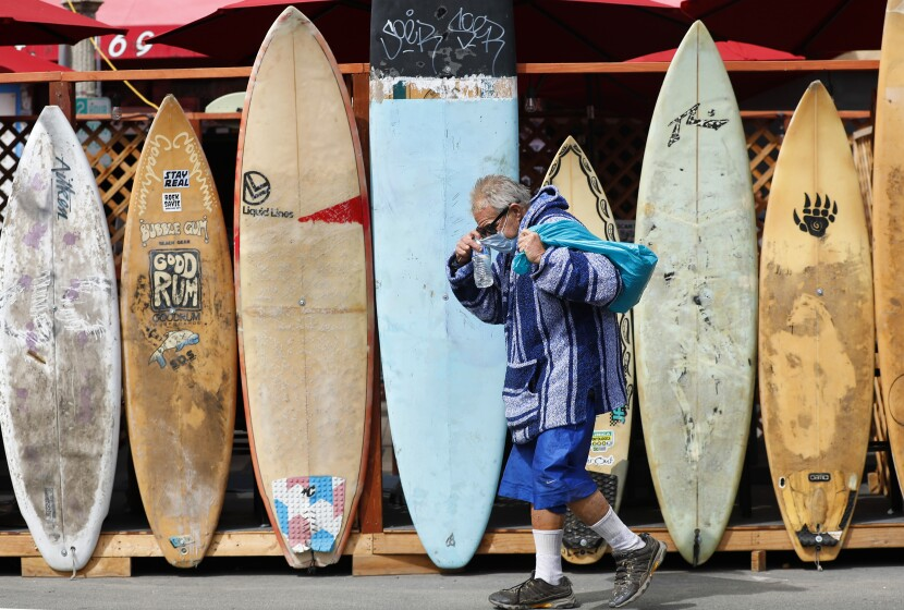 Eric Ross adjusts his mask as he walks by a line of surfboards used as a barrier.