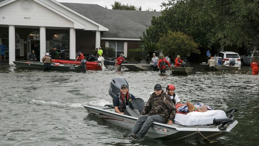 Volunteer boaters transport residents from the Cypress Glen nursing home in Port Arthur, Texas.