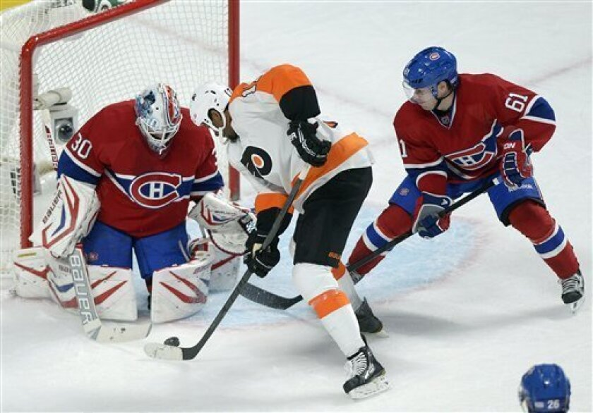 Montreal Canadiens' goaltender Peter Budaj, left, makes a save against Philadelphia Flyers' Wayne Simmonds as Canadiens' Raphael Diaz defends during the second period of an NHL hockey game in Montreal, on Saturday, Feb. 16, 2013. (AP Photo/The Canadian Press, Graham Hughes)