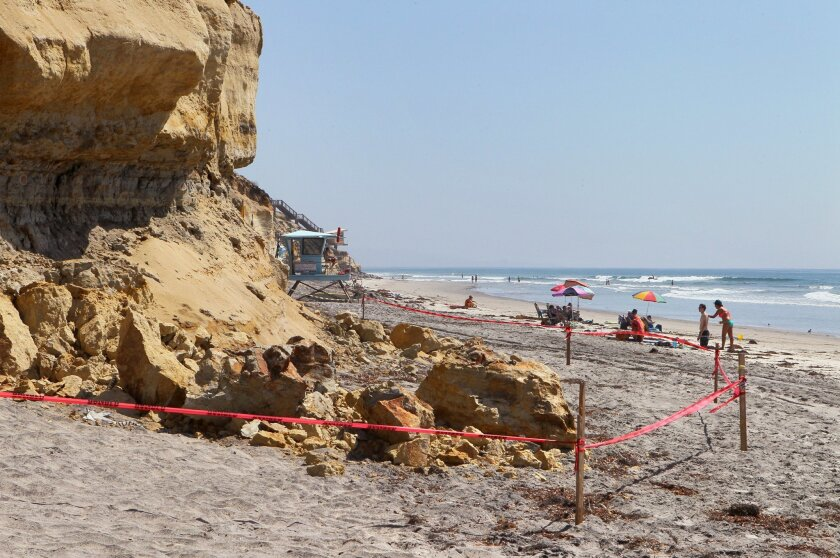 Warning tape keeps people away from a buff failure on the beach south of Fletcher Cove in Solana Beach.