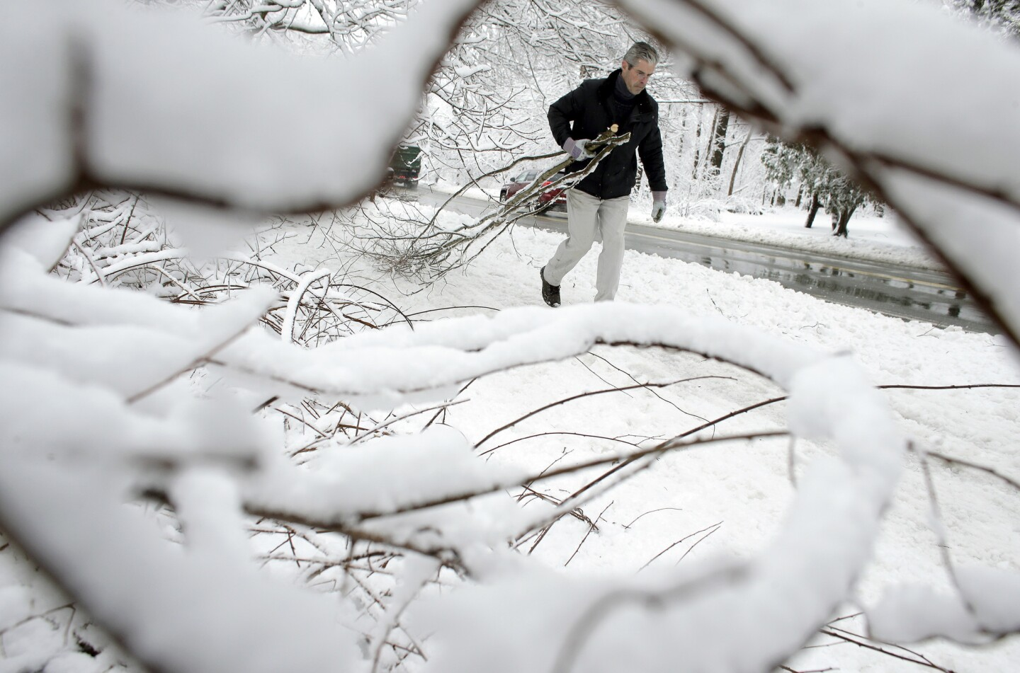 Kevin Crowley removes broken tree branches from a driveway in Sherborn, Mass., on March 8. For the second time in less than a week, a storm rolled into the Northeast with wet, heavy snow.