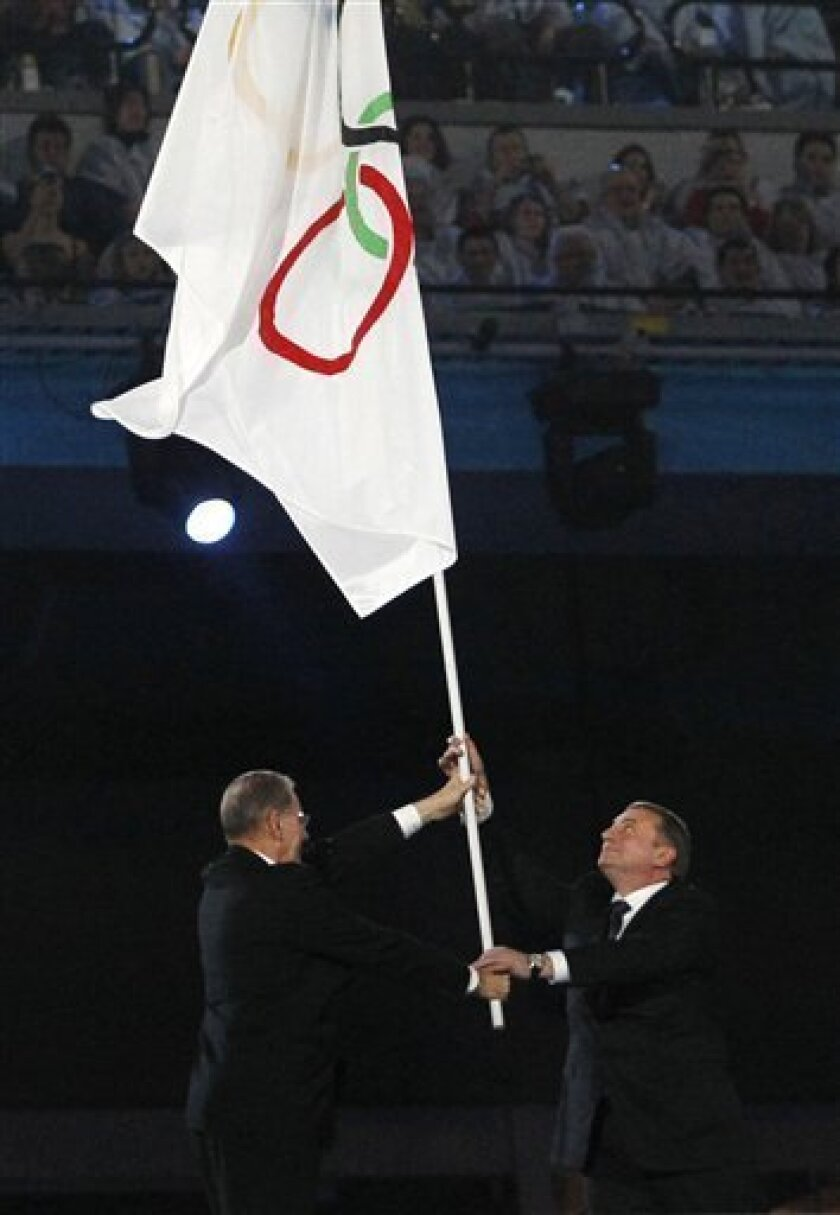 IOC President Jacques Rogge, left, hands over the Olympic flag the the mayor of Sochi Anatoly Pakhomov, right, during the closing ceremony for the Vancouver 2010 Olympics in Vancouver, British Columbia, Sunday, Feb. 28, 2010. (AP Photo/Matt Dunham)