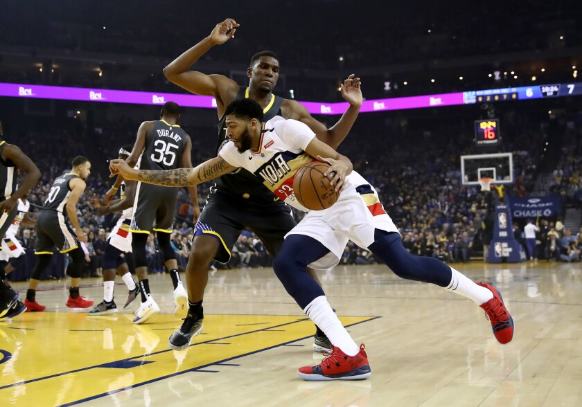 Anthony Davis #23 of the New Orleans Pelicans drives on Kevon Looney #5 of the Golden State Warriors at ORACLE Arena on January 16, 2019 in Oakland, California.