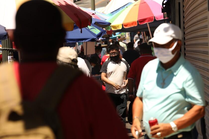 Masked customers shop along Alvarado Street near MacArthur Park in Los Angeles.