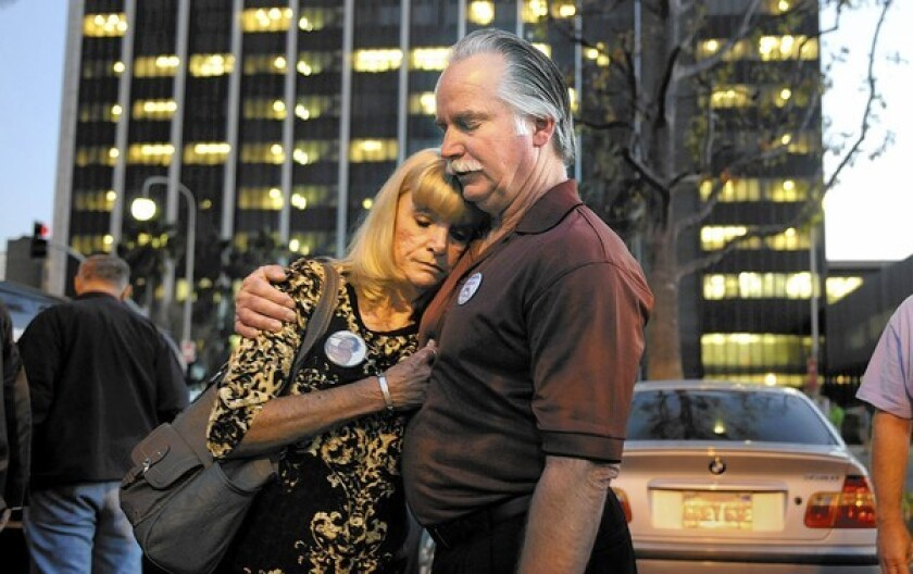 Ron and Kathy Thomas embrace outside the Santa Ana Courthouse Monday after two former Fullerton police officers were not guilty in the death of their son Kelly.