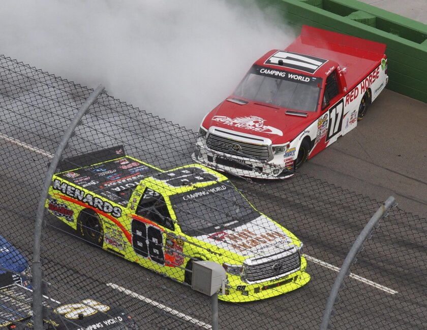 Camping World Truck Series driver Matt Crafton (88) passes by a spinning Timothy Peters (17) on the front stretch during the NASCAR Camping World Truck auto race at the Martinsville Speedway in Martinsville, Va., Saturday, Oct. 31, 2015.    (AP Photo/Steve Sheppard)