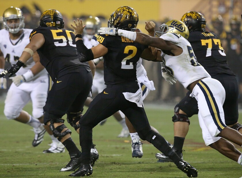 Bruins linebacker Deon Hollins strips the ball from Sun Devils quarterback Mike Bercovici in the third quarter.