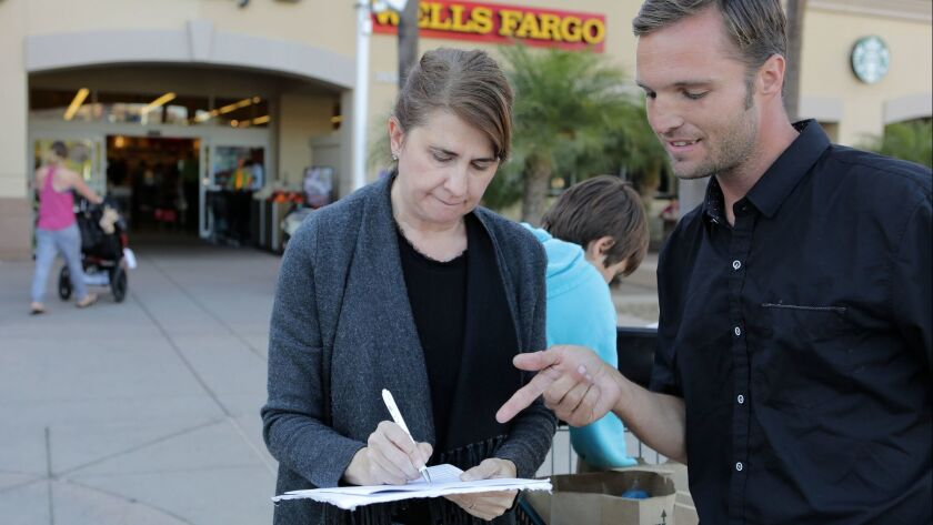 Robert Bush talks to Andrea Siler as she signs a petition for an initiative he is circulating on behalf of Yes! For A Better San Diego. The measure would raise the San Diego hotel tax to finance a convention center expansion and increased services and housing for the homeless.