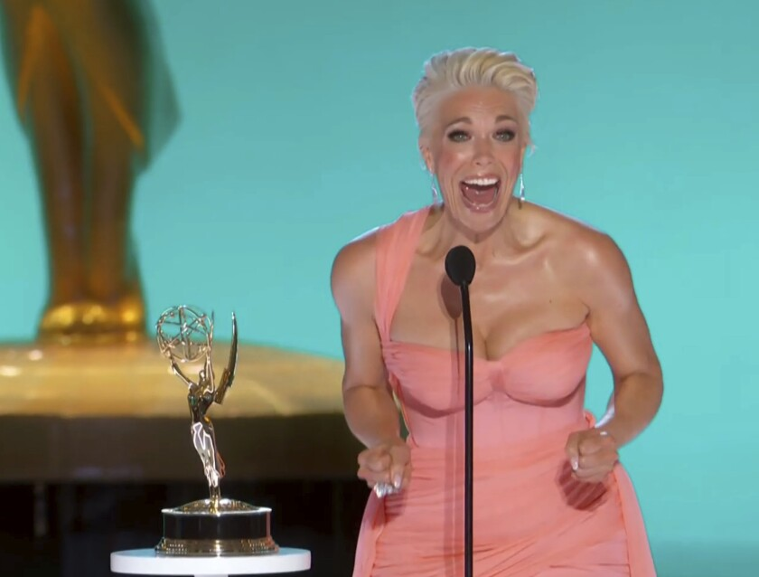 A woman in a pink dress screams happily behind a microphone
