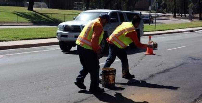 Putting sand over a repaired pothole, as crews did in April 2011, is the final step. Photo: Kathy Day
