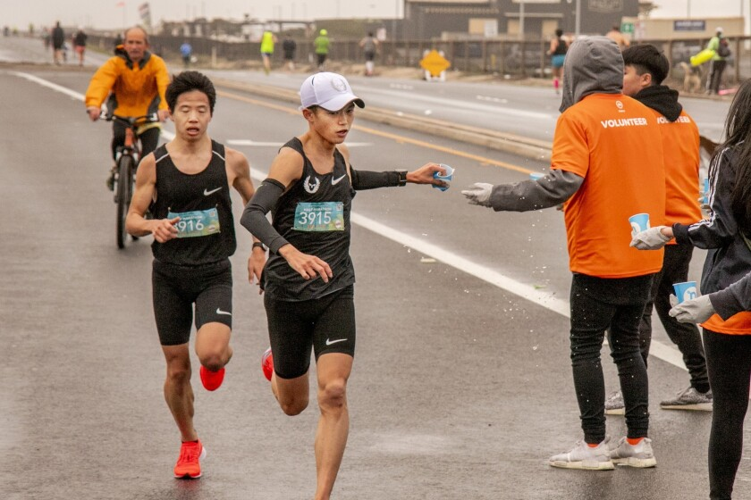 Suguru Osako reaches for a cup of water and Tetsuya Yoroizaka stays next to him as the two lead the Surf City men's half marathon in Huntington Beach Sunday.