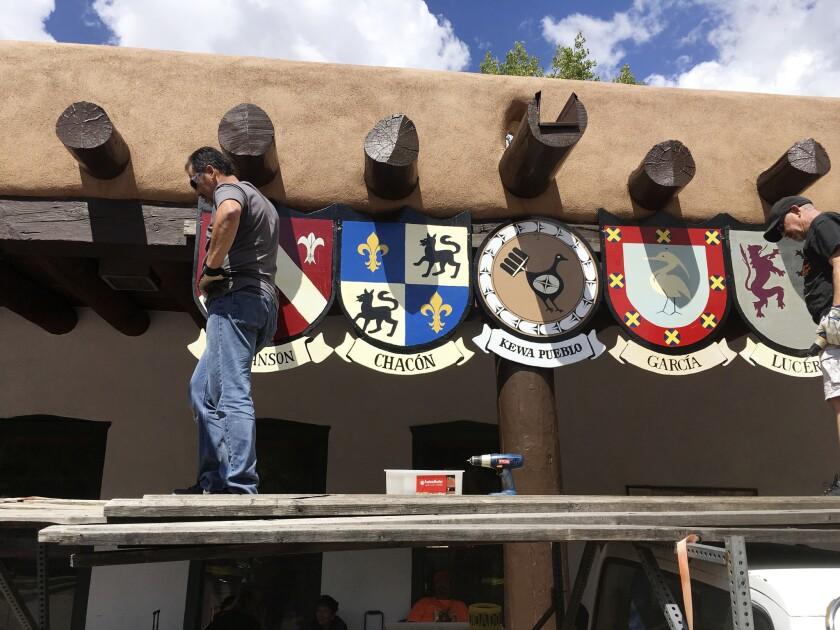 En esta fotografía del 1 de septiembre de 2016, organizadores de la Fiesta de Santa Fe colocan escudos de los apellidos de las primeras familias de pobladores españoles en el Palacio de los Gobernadores, en Santa Fe, New Mexico. Durante siglos, los habitantes hispanos del norte de New Mexico celebran una fiesta en Santa Fe para honrar al conquistador Don Diego de Vargas que recuperó la ciudad tras una revuelta indígena. (AP Foto/Russell Contreras)
