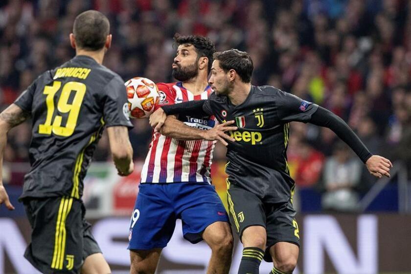 El delantero hispano-brasileño del Atlético de Madrid, Diego Costa (c), disputa el balón ante el defensa de la Juventus, Mattia De Sciglio (d), durante el encuentro correspondiente a la ida de los octavos de final de la Liga de Campeones que disputan anoche en el estadio Wanda Metropolitano, en Madrid. EFE