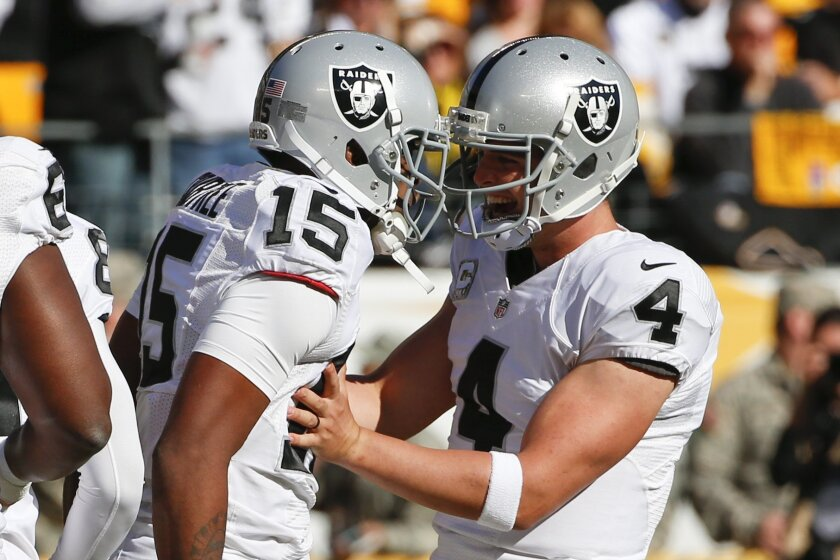 Oakland Raiders wide receiver Michael Crabtree (15) and quarterback Derek Carr (4)celebrate a touchdown pass in the first quarter of an NFL football game against the Pittsburgh Steelers, Sunday, Nov. 8, 2015, in Pittsburgh. (AP Photo/Gene J. Puskar)