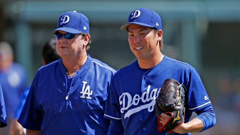 Los Angeles Dodgers starting pitcher Kenta Maeda, right, of Japan, walks with pitching coach Rick Ho