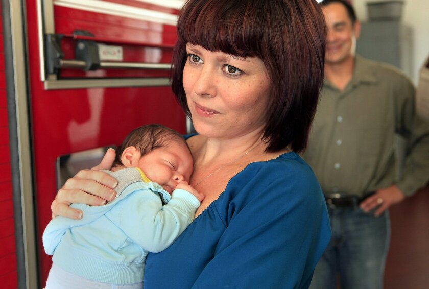 In this Feb. 17, 2014 photo, Melissa Wells-Pestana holds her 2-month-old baby Zavier Stephan Morgan Pestana at Oceanside's Fire Station 2 after a ceremony honoring firefighters who helped deliver him in Oceanside, Calif. She gave birth to before getting to the hospital thanks to the help of Oceansi