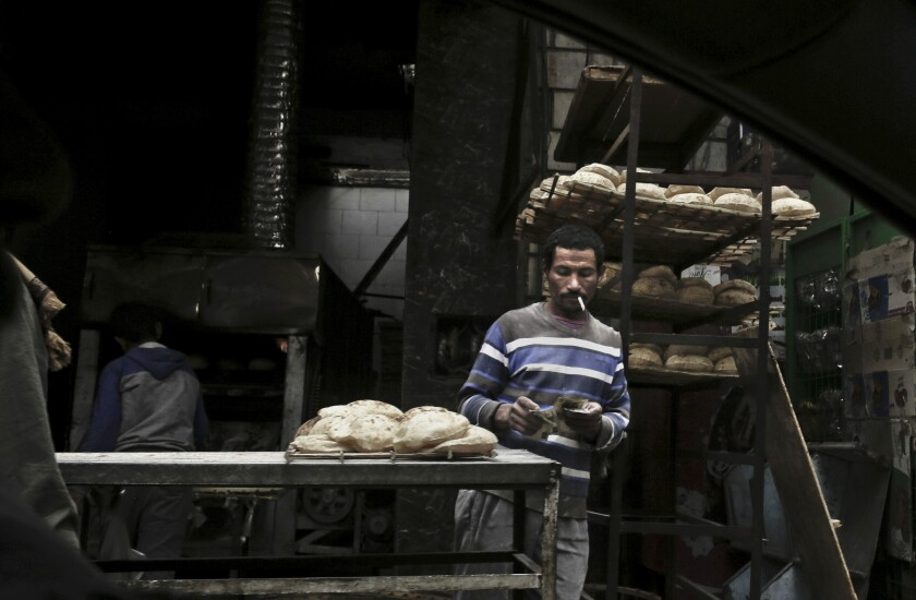 FILE - In this Feb. 14, 2017 file photo, a vendor counts his money at a bread stand in the Sayeda Zeinab neighborhood of Cairo, Egypt. On Tuesday, Aug. 3, 2021, Egyptian President Abdel Fattah el-Sissi has vowed to raise the price of government-subsidized bread, a move that would be the latest in a series of austerity measures taken by his government in recent years to overhaul the country's economy. El-Sissi offered no further details on the amount or timing of the increase. (AP Photo/Nariman El-Mofty, File)
