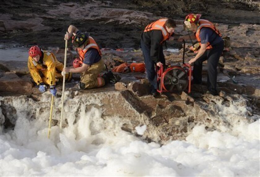 Rescuers search the Big Sioux River for two adults who went underwater after rescuing a boy who had fallen into the strong current, authorities said, Thursday, March 14, 2013 in Sioux Falls, S.D. (AP Photo/The Argus Leader, Elisha Page) NO SALES