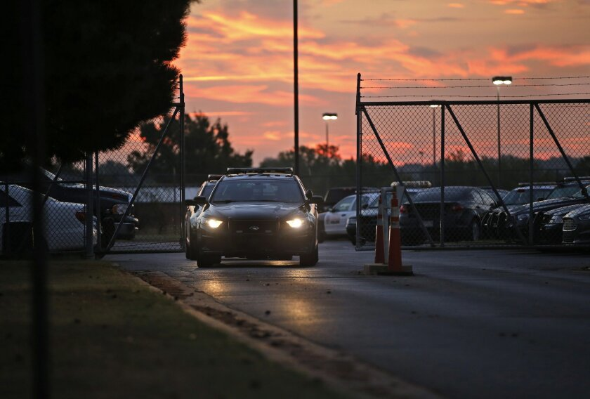 Police cars drive out of the Springlake Police Station at shift change in Oklahoma City on Oct. 7, 2015. A yearlong Associated Press investigation into sex abuse by cops, jail guards, deputies and other state law enforcement officials uncovered a broken system for policing bad officers, with signif