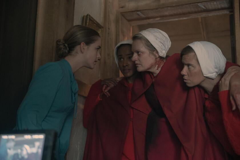 A woman in blue leans in to speak to an injured woman in red being carried by two others.