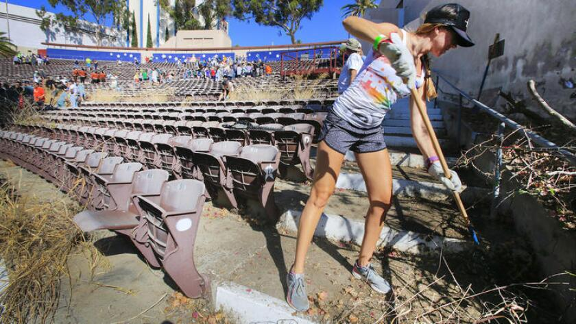 Lindsay Appelbaum of La Jolla helps clear out weeds and debris at the Starlight Bowl amphitheater in Balboa Park in 2016. (Howard Lipin / U-T file photo)
