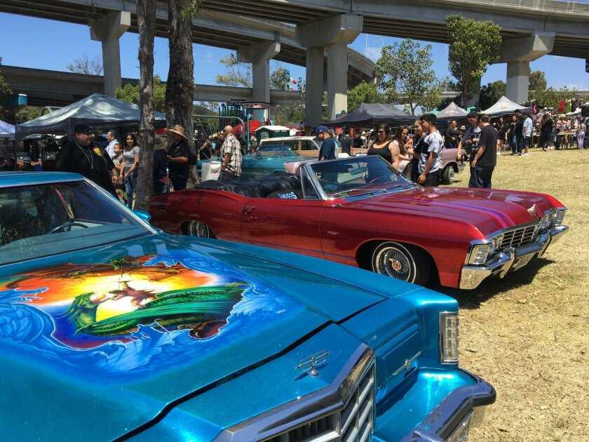 Event-goers admire customized cars Saturday at the 46th annual Chicano Park Day celebration in Barrio Logan. Cars on display were presented by individual car enthusiasts and Amigos Car Club.