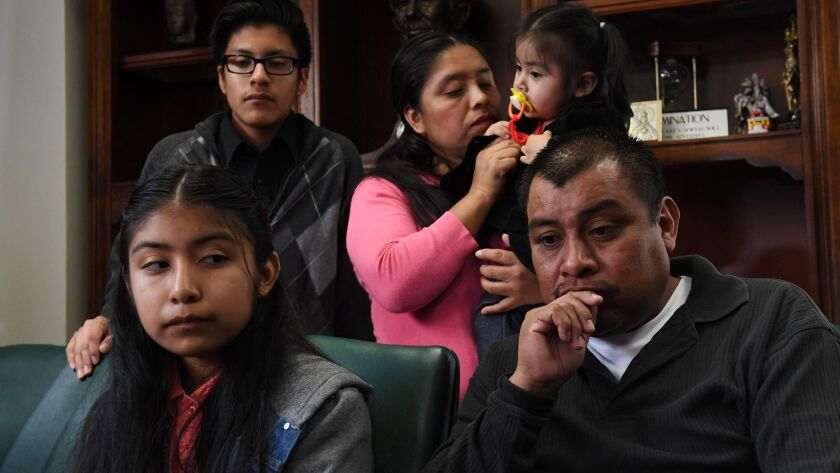 Immigrant Mario Vargas waits with his wife, Lola, and their daughter Athena in their attorney's office before Mario's deportation hearing.
