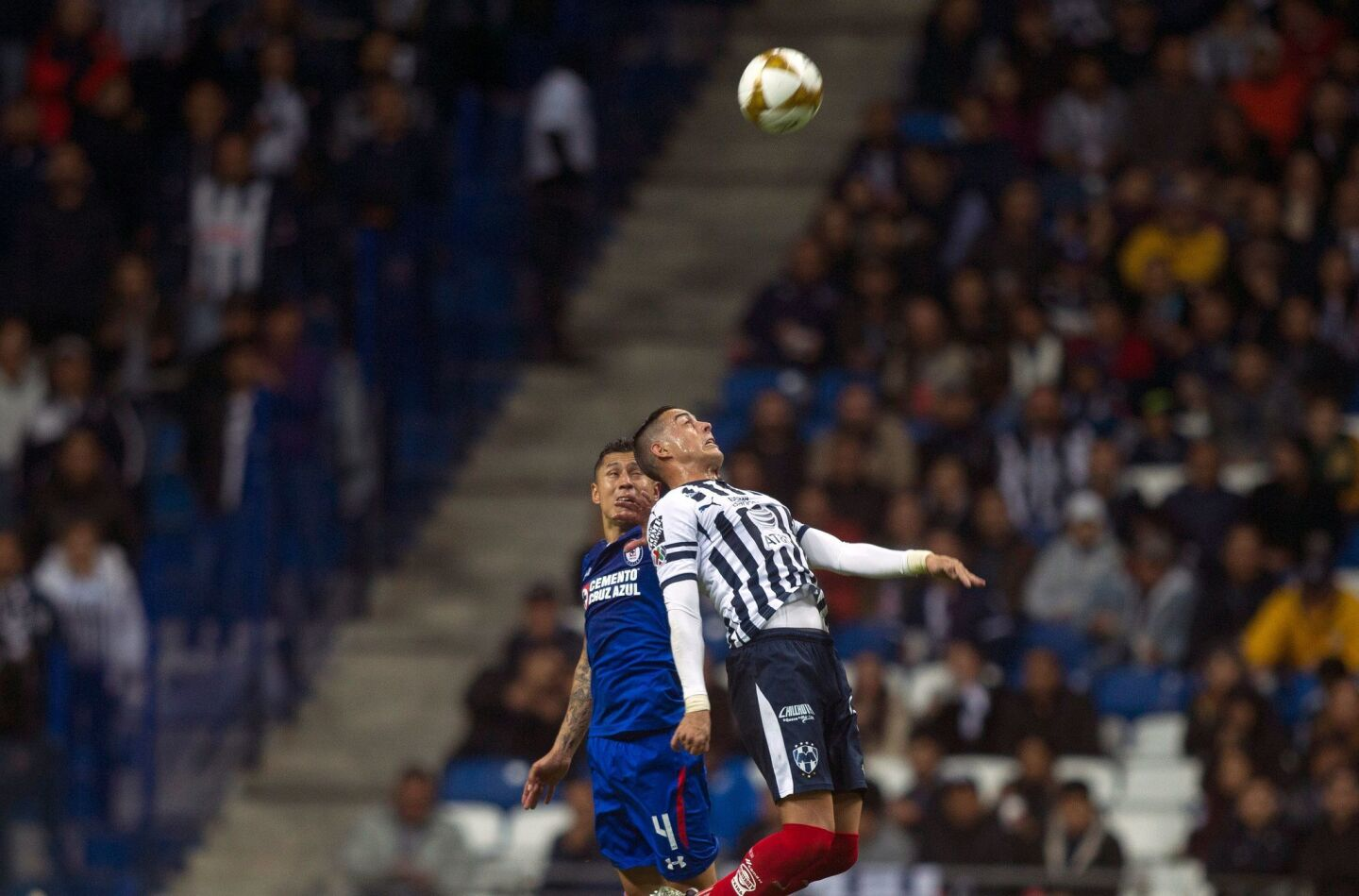 Monterrey's Argentinian foward Rogelio Funes Mori (R) jumps for a header with Cruz Azul's Mexican defender Julio Dominguez (L) during the first leg of the semifinal of the Mexican Apertura 2018 tournament football, match at the BBVA Bancomer stadium in Monterrey, Mexico on December 5, 2018. (Photo by Julio Cesar AGUILAR / AFP)JULIO CESAR AGUILAR/AFP/Getty Images ** OUTS - ELSENT, FPG, CM - OUTS * NM, PH, VA if sourced by CT, LA or MoD **
