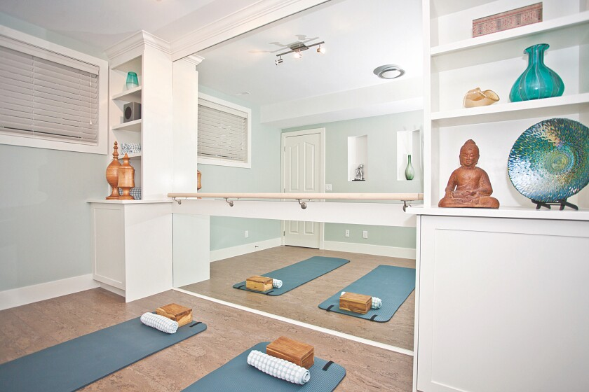 A bar, mirror, and stylish storage help create a welcoming, well-equipped home yoga space.