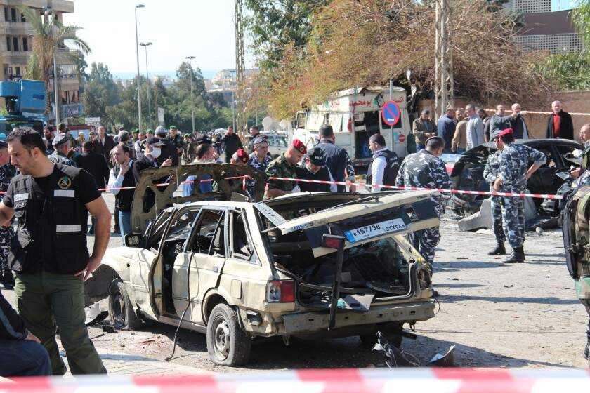 Authorities cordon off the site of a suicide car bomb attack in a crowded Beirut suburb.
