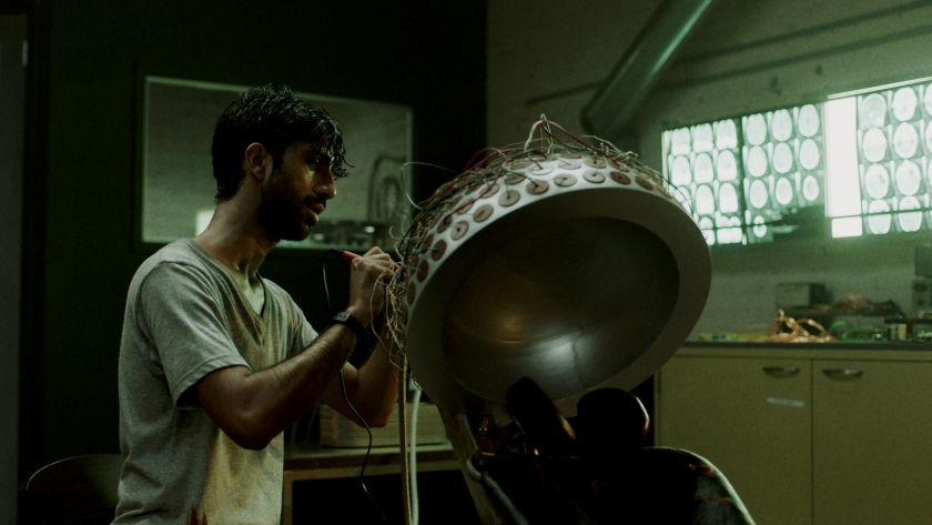 "Sathya Sridharan with his brain-altering device in the thriller ""Minor Premise."""