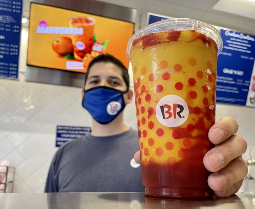 Héctor Ruiz, 29, holds a mangonada at his Baskin-Robbins franchise in Imperial Beach.