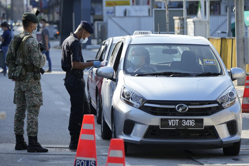 Police check passengers in vehicles at a roadblock during the first day of Full Movement Control Order (MCO) in Kuala Lumpur, Malaysia, Tuesday, June 1, 2021. Malls and most businesses in Malaysia shuttered Tuesday as the country began its second near total coronavirus lockdown to tackle a worsening pandemic that has put its healthcare system on the verge of collapse. (AP Photo/Vincent Thian)