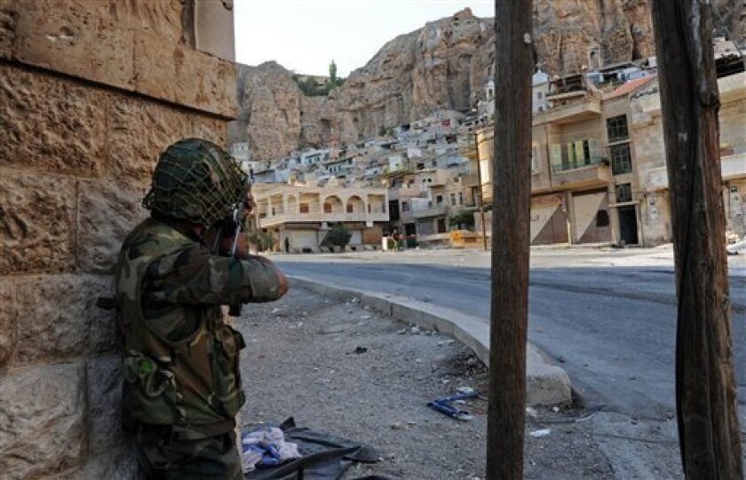 In this Wednesday, Sept. 11, 2013 photo released by the Syrian official news agency SANA, a Syrian government solider aims his weapon during clashes with Free Syrian Army fighters, not pictured, in Maaloula village, northeast of the capital Damascus, Syria. Heavy fighting between Syrian government troops and rebels flared again on Wednesday, Sept. 11, 2013 in the ancient, predominantly Christian village of Maaloula. Troops are trying to flush out rebel units, including two that are linked to al-