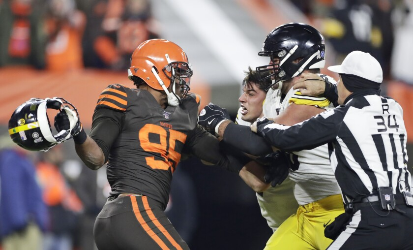 Myles Garrett of the Cleveland Browns, left, holds Mason Rudolph's helmet just before hitting Rudolph, center, in the head with it.