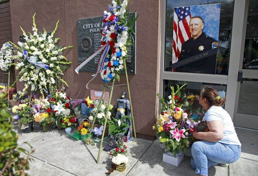 Hayward resident Hilda Sierra moves some flowers under the portrait of fallen Sgt. Scott Lunger outside the Hayward Police Department in Hayward, Calif., on Wednesday, July 22, 2015. Lunger was shot and killed early Wednesday morning during a routine traffic stop. (Laura A. Oda/The Oakland Tribune via AP)