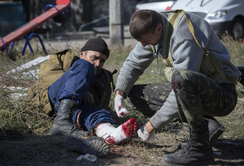A pro-Russian rebel injured by shrapnel gets a field dressing after action near to the airport in the town of Donetsk, eastern Ukraine Tuesday, Oct. 7, 2014. Despite a cease-fire declared a month ago between the Ukrainian forces and pro-Russian rebels, the biggest city in eastern Ukraine remains embroiled in fighting . (AP Photo/Dmitry Lovetsky)