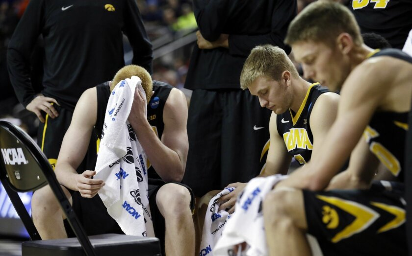 FILE - In this March 22, 2015, file photo, Iowa's Aaron White, left, and teammates rest during a timeout against Gonzaga in the second half of an NCAA tournament college basketball game in the Round of 32 in Seattle. In the NCAA tournament, more frequent stoppages in play-- leave coaches and player