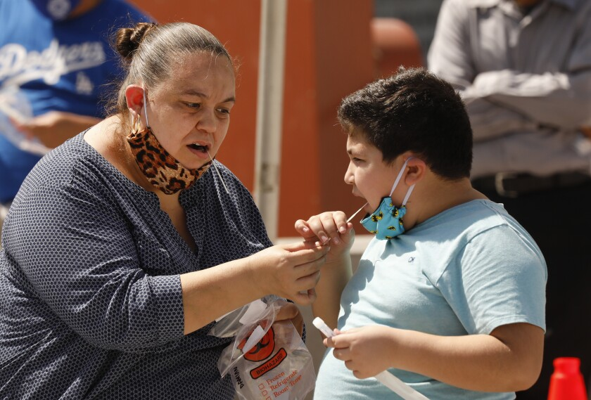 Edna Orante, 42, helps her son Damian Orante, 9, administer an oral swab test in Los Angeles
