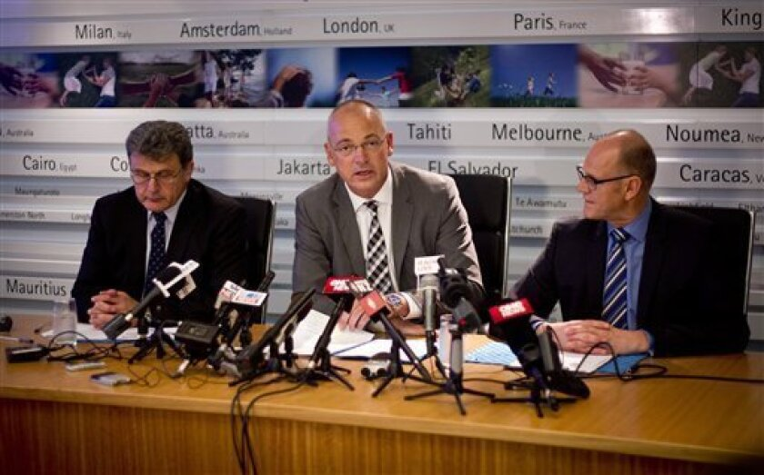 FILE - In this Wednesday, Aug. 7, 2013 file photo, Fonterra Chief Executive Theo Spierings, center, accompanied by Fonterra's head of New Zealand Milk Products Gary Romano, left, and Kerry Underhill, head of communications, hold a press conference in Auckland, New Zealand. Senior manager Romano resigned Wednesday, Aug. 14, in the wake of a botulism scare. Fonterra said Romano had already left the company. In his role as managing director of New Zealand Milk Products, Romano oversaw the tainted p