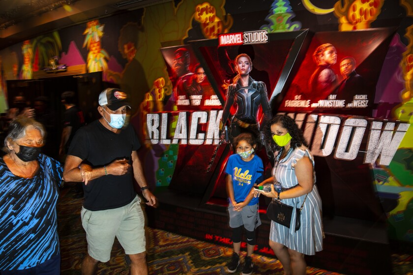 """Masked patrons walk past a lobby display for Marvel Studios' """"Black Widow,"""" on opening weekend at the El Capitan Theatre"""