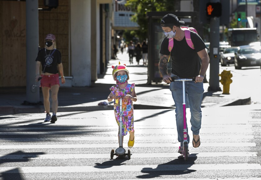 People wear protective masks while riding scooters in Studio City, Calif., last week.