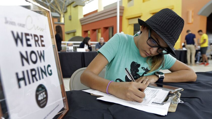 FILE - In this Oct. 3, 2017 file photo, job seeker Alejandra Bastidas fills out an application at a